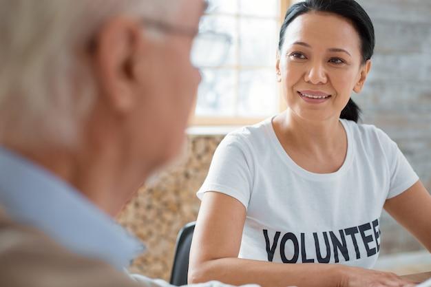 Ciekawa rozmowa. apelujący wolontariusz-wesoły, szczerzący się, rozmawiając ze starszym mężczyzną i patrząc na niego