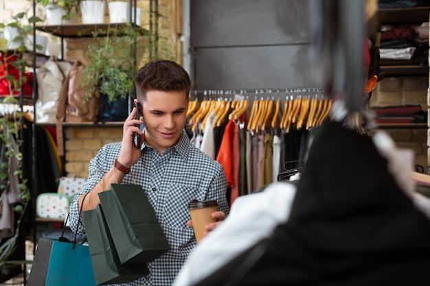 Ciekawa rozmowa. spokojny, zrelaksowany młody człowiek w zamyśleniu przyglądający się modnym ciuchom w popularnym sklepie i rozmawiający przez telefon