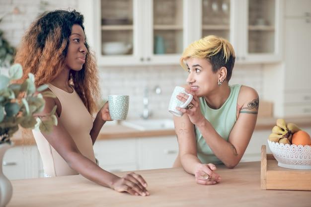 Ciekawa rozmowa. uśmiechający się długowłosy amarykańczyk i zaskoczony kaukaski dziewczyna z krótkimi farbowanymi włosami pije kawę w kuchni