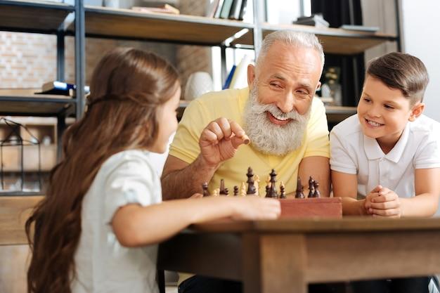 Ciekawa rozrywka. słodki chłopiec i dziewczynka w wieku przedszkolnym słuchają uśmiechniętego dziadka trzymającego pionek i wyjaśniającego im zasady gry w szachy
