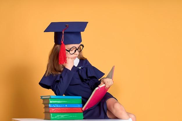 Ciekawa uczennica w stroju ukończenia nauki z podręczników