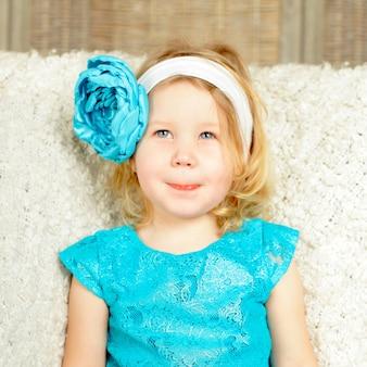 Ciekawa uśmiechnięta dziecko dziewczyna z niebieskim kwiatem
