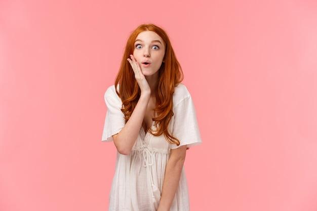 Ciekawa, zafascynowana urocza europejska rudowłosa kobieta w białej sukni, policzku i westchnieniu