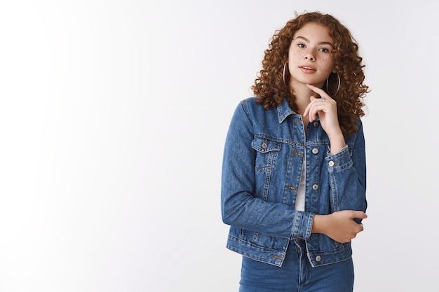 Ciekawa zainteresowana urocza studentka kręcone włosy ruda dziewczyna piegi pryszcze słuchać wykładu stojąc zaintrygowana skupiona otwarte usta dotknąć szyi zamyślona, myśląca białe tło