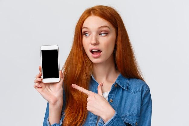 Ciekawa, zastanawiająca się ładna rudowłosa kaukaska kobieta pokazująca zdjęcia z wakacji, wskazująca na wyświetlacz smartfona zerkająca na ekran, stojąca rozbawiona na białej ścianie, polecam aplikację