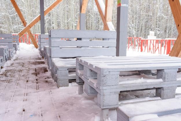 Ciekawa zimowa kawiarnia, w której stoły i krzesła wykonane są z drewnianych palet. pusta, zaśnieżona kawiarnia o oryginalnym wystroju.
