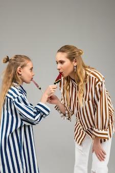 Ciekawe, dobrze wyglądające panie w odjechanych koszulach, próbujące nawzajem słodyczy w kształcie arbuza