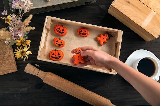 Ciekawe halloweenowe imbirowe ciasteczka w kształcie dyni leżą w formie do gotowania. ciasteczka w ręku. pyszne z kawą.