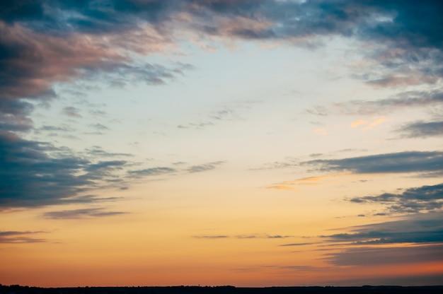 Ciekawe krajobrazowe niebo zachód słońca. niebieskie chmury rozchodzą się przed czerwonym niebem. fascynujący moment.