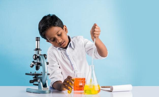 Ciekawe małe indyjskie dzieci w wieku szkolnym lub naukowcy studiujący nauki ścisłe, eksperymentujące z chemikaliami lub mikroskopem w laboratorium, selektywne ogniskowanie