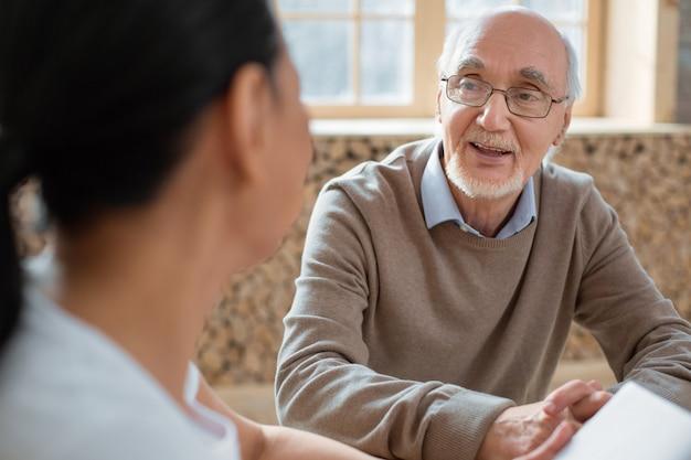 Ciekawe myśli. uroczy przystojny starszy mężczyzna uśmiecha się podczas słuchania wolontariusza i pozowanie na niewyraźne tło