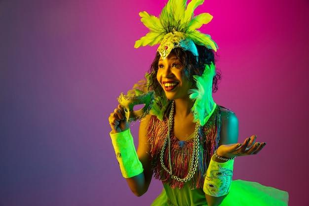 Ciekawe. piękna młoda kobieta w karnawale, stylowy kostium maskarady z piórami tańczącymi na ścianie gradientu w neonie. koncepcja obchodów świąt, czasu świątecznego, tańca, imprezy, zabawy.