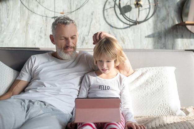 Ciekawe tutaj. uważny zainteresowany tata i dziecko, patrząc na ekran tabletu, siedząc na łóżku w domu