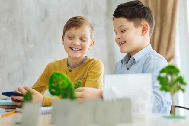Ciekawe zadanie domowe. dwóch optymistycznych chłopców w wieku przedszkolnym siedzących przy stole i wspólnie tworzących model miniaturowej dzielnicy do swojego projektu ekologicznego