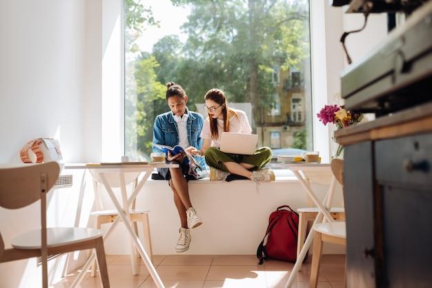 Ciekawe zadanie. wesoła długowłosa dziewczyna siedzi obok koleżanki i wskazuje na potrzebny tekst