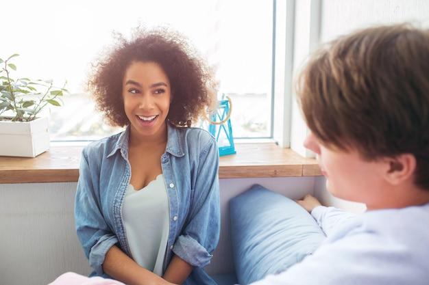 Ciekawe zdjęcie afroamerykańskiej dziewczyny siedzi razem z facetem. patrzy na niego i uśmiecha się. on na nią patrzy.