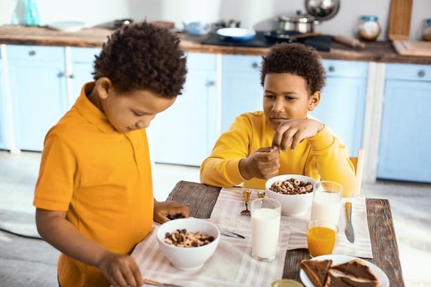 Ciekawi mnie śniadanie. uroczy chłopcy z kręconymi włosami siedzą przy stole i oglądają płatki śniadaniowe