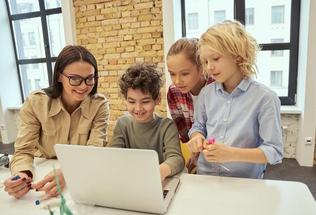 Ciekawi uczący się młoda nauczycielka w okularach pokazująca naukowy film o robotyce do radości