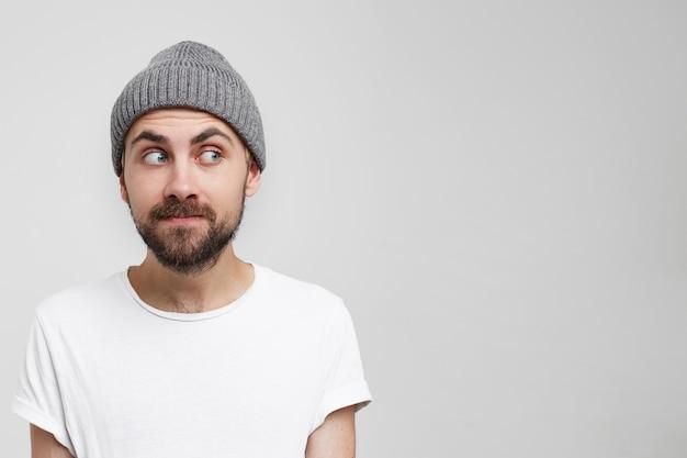Ciekawie portret młodego mężczyzny w szarej czapce