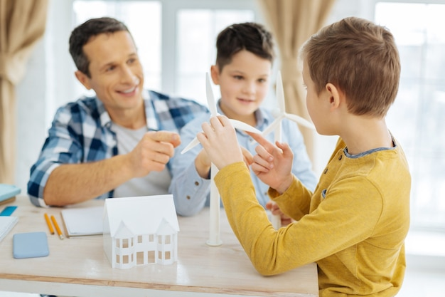 Ciekawość dziecięca. uroczy chłopiec w wieku przedszkolnym siedzi przy stole z ojcem i bratem i pyta ojca o budowę turbin wiatrowych