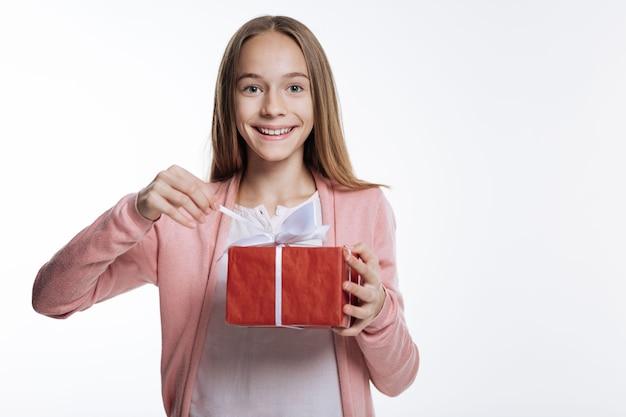 Ciekawość dziecięca. wesoła nastolatka trzymająca pudełko i pociągając za sznurek, chcąc otworzyć pudełko, uśmiechając się na szaro