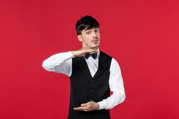 Ciekawski męski kelner w mundurze z motylem na szyi na czerwonym tle