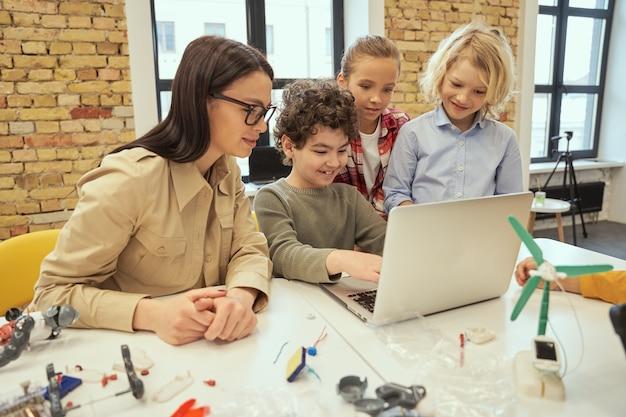 Ciekawskie dzieci korzystające z laptopa oglądają naukowe wideo na temat robotyki siedzące przy stole w klasie