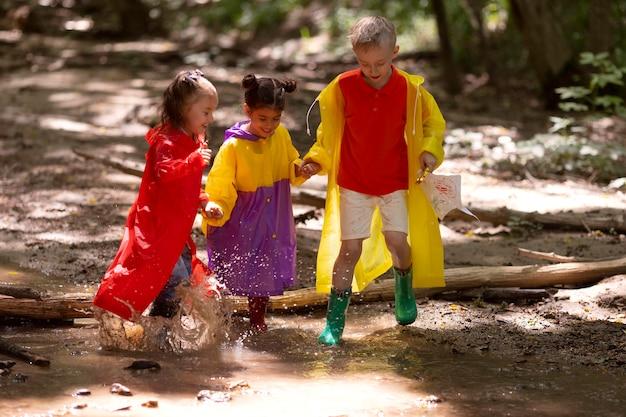 Ciekawskie dzieci uczestniczące w poszukiwaniu skarbów w lesie