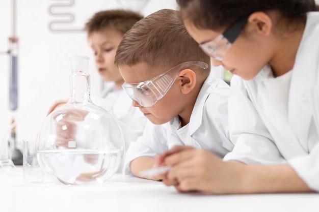 Ciekawskie dzieciaki robią eksperyment chemiczny w szkole