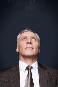 Ciekawy biznesmen. portret ciekawskiego starszego mężczyzny w formalwear patrząc w górę stojąc przed tablicą