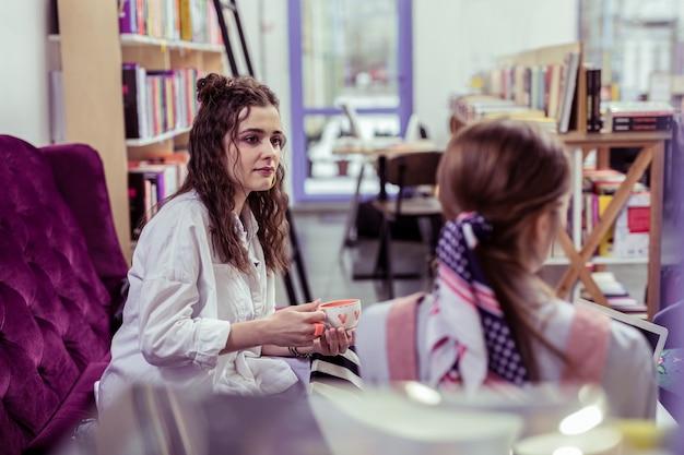 Ciekawy bliski przyjaciel. poważna piękna dziewczyna z dwiema bułeczkami patrzy na rozmawiającego przyjaciela, niosąc filiżankę herbaty
