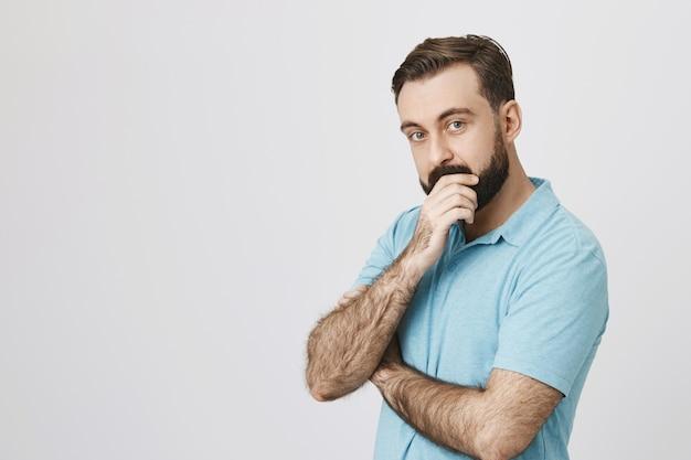 Ciekawy brodaty mężczyzna podejmuje decyzje, myśli i wygląda zamyślony