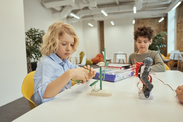 Ciekawy chłopiec kaukaski oglądający zabawkę techniczną pełną szczegółów, siedząc razem przy stole