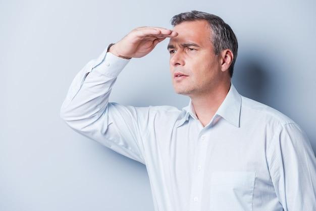 Ciekawy dojrzały mężczyzna. widok z boku ciekawego dojrzałego mężczyzny w koszuli, patrzącego na widok, trzymającego rękę nad oczami i stojącego na szarym tle