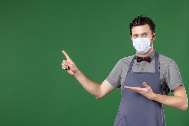 Ciekawy facet kelner w mundurze z maską medyczną i wskazujący na prawą stronę na zielonym tle