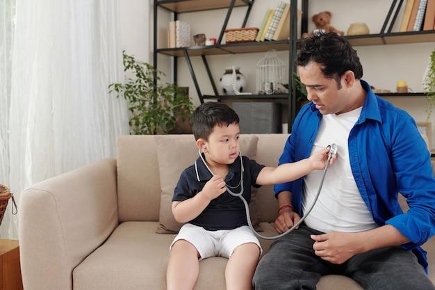 Ciekawy mały chłopiec siedzi na kanapie ze stetoskopem i słucha bicia serca swojego ojca