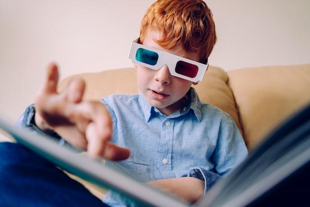 Ciekawy mały chłopiec w okularach trójwymiarowych i czytający interaktywną książkę w domu. książki edukacyjne i zajęcia edukacyjne dla dzieci aktywnych intelektualnie. doświadcz nowych wrażeń.