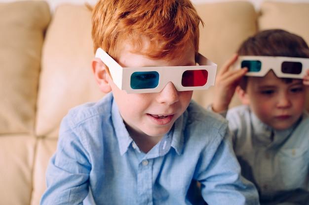 Ciekawy mały chłopiec w okularach trójwymiarowych i czytający interaktywną książkę w domu.