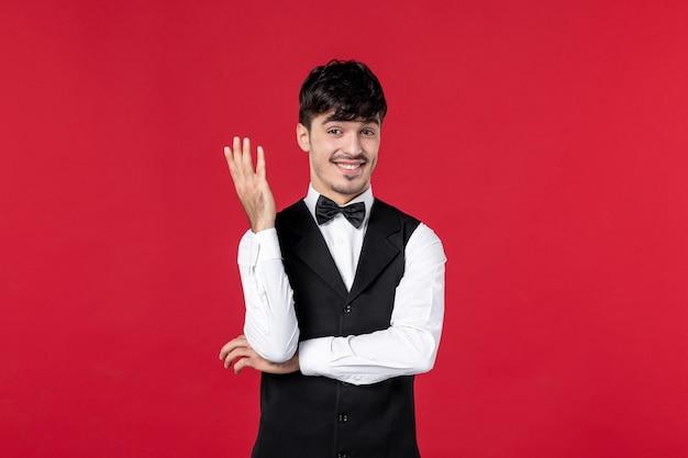 Ciekawy męski kelner w mundurze z motylem na szyi na czerwonym tle
