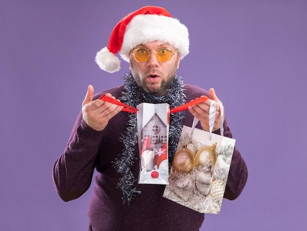 Ciekawy mężczyzna w średnim wieku ubrany w czapkę mikołaja i świecącą girlandę na szyi w okularach trzyma torby na prezenty świąteczne, otwierając jeden patrząc na aparat odizolowany na fioletowym tle