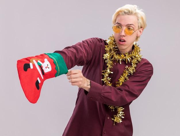 Ciekawy młody blondyn w okularach z świecącą girlandą na szyi trzyma świąteczną skarpetę, patrząc na nią, wkładając rękę do niej na białym tle