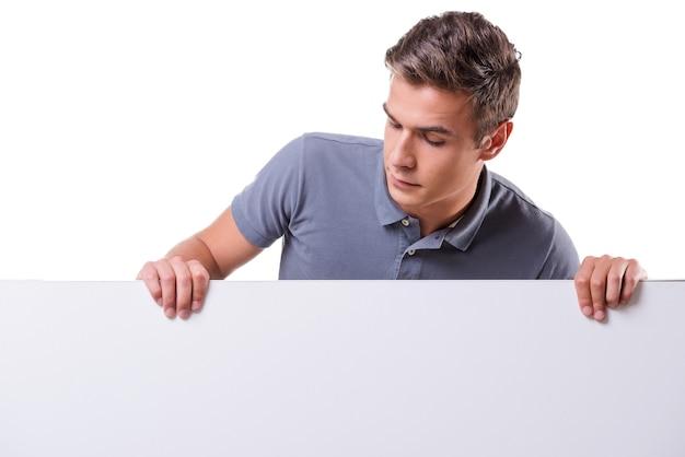 Ciekawy młody człowiek. przystojny młody mężczyzna oparty na przestrzeni kopii i patrzący na nią