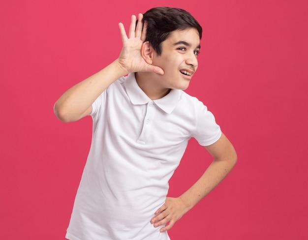 Ciekawy młody kaukaski chłopiec trzymający rękę na talii, patrząc prosto, nie słyszę, jak gestykulujesz na różowej ścianie z kopią przestrzeni