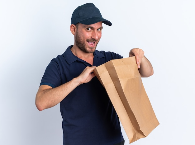 Ciekawy młody kaukaski dostawca w niebieskim mundurze i czapce otwierającej papierowe opakowanie