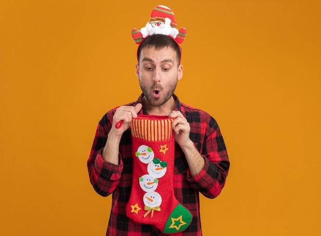 Ciekawy młody kaukaski mężczyzna ubrany w opaskę świętego mikołaja trzyma skarpetę świąteczną, otwierając ją, patrząc wewnątrz niej na białym tle na pomarańczowej ścianie z miejsca na kopię