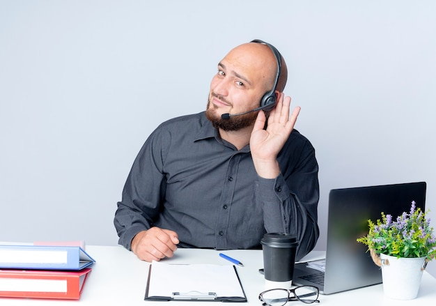 Ciekawy młody łysy mężczyzna call center sobie zestaw słuchawkowy siedzi przy biurku z narzędzi pracy robi nie słyszy, jak gest na białym tle