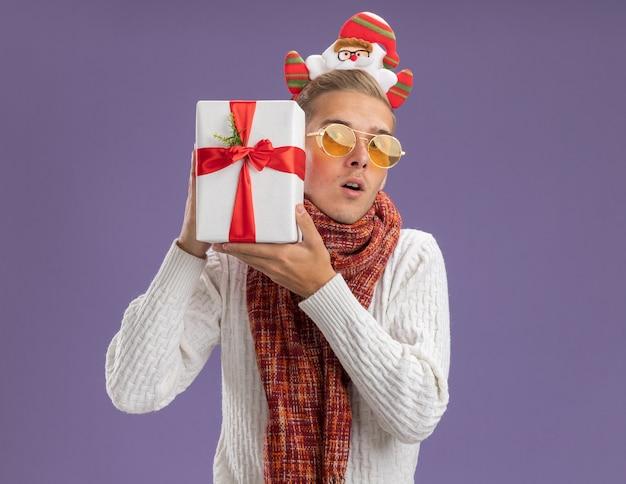 Ciekawy młody przystojny facet ubrany w opaskę świętego mikołaja i szalik trzyma paczkę prezentów blisko głowy patrząc na aparat odizolowany na fioletowym tle