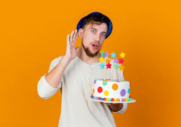 Ciekawy młody przystojny słowiański imprezowicz w kapeluszu imprezowym, trzymając tort urodzinowy z gwiazdami, patrząc na kamerę, robiący, nie słyszy cię gestu na białym tle na pomarańczowym tle z miejsca na kopię