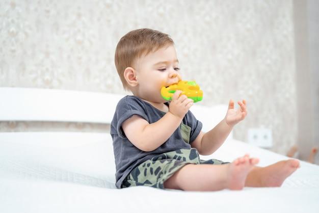 Ciekawy niemowlę chłopiec gryząca grzechotka siedząca na łóżku w słonecznej sypialni dziecko gryzie plastikową zabawkę