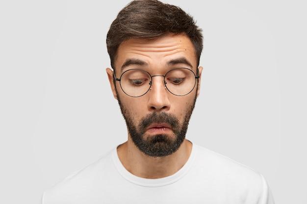 Ciekawy nieogolony robotnik skupił się, patrzy z zaciekawieniem, gdy coś zauważa, zastanawia się, będąc w białej koszulce i okrągłych okularach, pozuje samotnie na białej ścianie. wyrazy twarzy